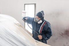 Πρατήριο βενζίνης αυτοκινήτων Εργαζόμενος που χρωματίζει ένα άσπρο αυτοκίνητο στο ειδικό γκαράζ, που φορά το κοστούμι και το προσ στοκ φωτογραφία