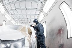 Πρατήριο βενζίνης αυτοκινήτων Εργαζόμενος που χρωματίζει ένα άσπρο αυτοκίνητο στο ειδικό γκαράζ, που φορά το κοστούμι και το προσ στοκ φωτογραφίες με δικαίωμα ελεύθερης χρήσης