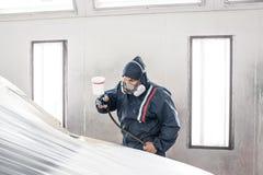 Πρατήριο βενζίνης αυτοκινήτων Εργαζόμενος που χρωματίζει ένα άσπρο αυτοκίνητο στο ειδικό γκαράζ, που φορά το κοστούμι και το προσ στοκ φωτογραφία με δικαίωμα ελεύθερης χρήσης
