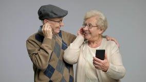 Πρεσβύτεροι που ακούνε τη μουσική σε ένα τηλέφωνο απόθεμα βίντεο