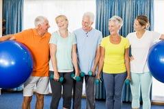 Πρεσβύτεροι που κρατούν τη σφαίρα και τα βάρη άσκησης στοκ φωτογραφίες