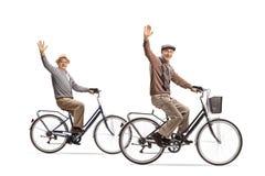 Πρεσβύτεροι που οδηγούν τα ποδήλατα και που κυματίζουν στη κάμερα Στοκ Εικόνες