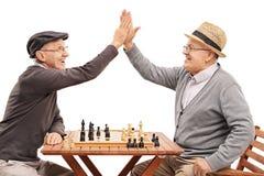 Πρεσβύτεροι που παίζουν το σκάκι και υψηλός-πέντε μεταξύ τους στοκ εικόνες