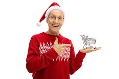Πρεσβύτερος με το καπέλο Χριστουγέννων που κρατά το μικρό κενό κάρρο αγορών και Στοκ Φωτογραφία