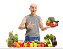 Πρεσβύτερος πίσω από έναν πίνακα με τα φρούτα και λαχανικά που κρατούν ένα πιάτο Στοκ εικόνα με δικαίωμα ελεύθερης χρήσης