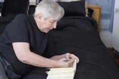 Πρεσβύτερος που γράφει από το κρεβάτι του στοκ εικόνες