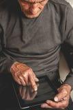 Πρεσβύτερος που κρατά μια ταμπλέτα στα χέρια Στοκ Εικόνα