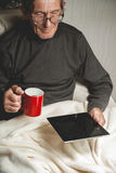 Πρεσβύτερος που κρατά μια ταμπλέτα στα χέρια Στοκ εικόνες με δικαίωμα ελεύθερης χρήσης