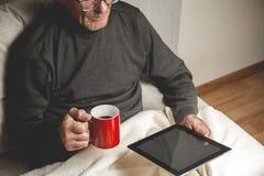Πρεσβύτερος που κρατά μια ταμπλέτα στα χέρια Στοκ Φωτογραφία