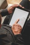 Πρεσβύτερος που κρατά μια ταμπλέτα στα χέρια Στοκ Εικόνες