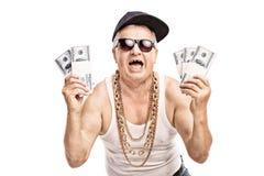 Πρεσβύτερος στην εξάρτηση χιπ χοπ που κρατά μερικούς σωρούς των χρημάτων στοκ φωτογραφίες