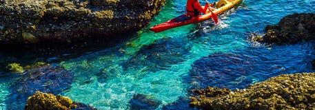 Πρεσβύτερος kayaker σε ένα καγιάκ από τη θάλασσα, τον ενεργούς αθλητισμό νερού και το lei Στοκ Φωτογραφίες
