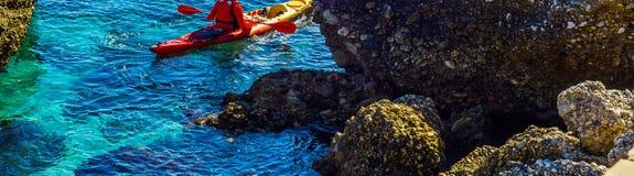 Πρεσβύτερος kayaker σε ένα καγιάκ από τη θάλασσα, τον ενεργούς αθλητισμό νερού και το lei Στοκ Εικόνα