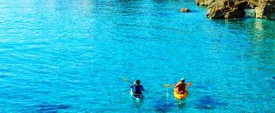 Πρεσβύτερος kayaker σε ένα καγιάκ από τη θάλασσα, τον ενεργούς αθλητισμό νερού και το lei Στοκ εικόνες με δικαίωμα ελεύθερης χρήσης