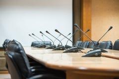 Πριν από μια διάσκεψη, τα μικρόφωνα μπροστά από τις κενές έδρες Στοκ Εικόνες