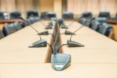 Πριν από μια διάσκεψη, τα μικρόφωνα μπροστά από τις κενές έδρες S Στοκ Φωτογραφία