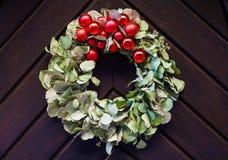 Πριν από τα Χριστούγεννα ένα στεφάνι εμφάνισης που κρεμά σε μια ξύλινη πόρτα Στοκ Φωτογραφίες