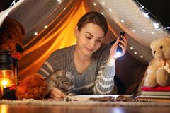 Πριν από την ώρα για ύπνο Ένα κορίτσι με μια σκωτσέζικη και βρετανική γάτα που διαβάζει ένα βιβλίο σε μια σκηνή Μια έννοια του υπ στοκ εικόνες με δικαίωμα ελεύθερης χρήσης