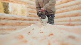 Πριονίζοντας κούτσουρα αλυσιδοπριόνων ξυλουργών λειτουργώντας για τα ξύλινα σπίτια Καναδική τεκτονική γωνίας Καναδικό ύφος απόθεμα βίντεο