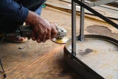 Πριονίζοντας μέταλλο εργαζομένων με έναν μύλο, εργαζόμενος που ενώνει στενά το χάλυβα, έκδοση 14 Στοκ Φωτογραφία