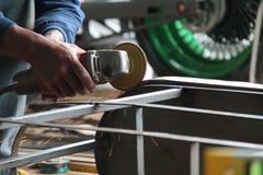 Πριονίζοντας μέταλλο εργαζομένων με έναν μύλο, εργαζόμενος που ενώνει στενά το χάλυβα, έκδοση 17 Στοκ Φωτογραφία
