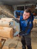 Πριονίζοντας ξύλο ξυλουργών με ένα αλυσιδοπρίονο Στοκ Εικόνα