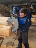 Πριονίζοντας ξύλο ξυλουργών με ένα αλυσιδοπρίονο Στοκ φωτογραφία με δικαίωμα ελεύθερης χρήσης