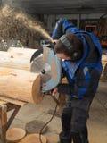 Πριονίζοντας ξύλο ξυλουργών με ένα αλυσιδοπρίονο Στοκ εικόνες με δικαίωμα ελεύθερης χρήσης