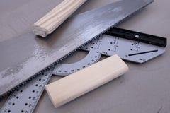 Πριόνι με το μοιρογνωμόνιο και τα κομμάτια του ξύλου Στοκ Εικόνες