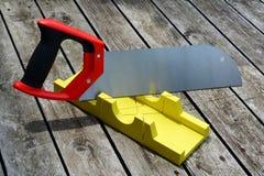 Πριόνι χεριών και ένα κίτρινο miter κιβώτιο για να κάνει ακριβής να συνδέσει λοξά τις περικοπές στοκ εικόνες με δικαίωμα ελεύθερης χρήσης