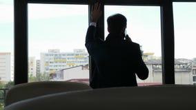Προβληματικός επιχειρηματίας στη σκιαγραφία που μιλά στο τηλέφωνο απόθεμα βίντεο