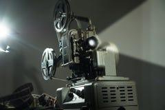 Προβολέας κινηματογράφων με μια ταινία στο σκοτεινό υπόβαθρο στοκ φωτογραφίες