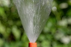 Προβολή ύδατος από hosepipe με ένα πράσινο υπόβαθρο στοκ εικόνες