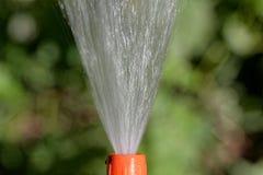 Προβολή ύδατος από hosepipe με ένα πράσινο υπόβαθρο στοκ εικόνα