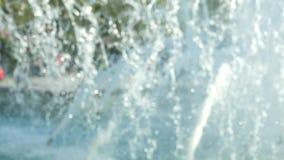 Προβολή ύδατος πηγών πόλεων σε ένα θολωμένο υπόβαθρο με τους ανθρώπους που περπατούν γύρω από τις πηγές στο κέντρο πόλεων φιλμ μικρού μήκους