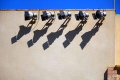 Προβολείς ή επίκεντρα σε έναν λαμπρά αναμμένο εξωτερικό τοίχο, castin στοκ φωτογραφία