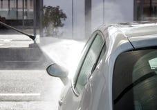 Προβολή ύδατος πίεσης πέρα από το άσπρο δευτερεύον παράθυρο αυτοκινήτων στο πλύσιμο αυτοκινήτων Στοκ Εικόνες