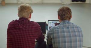 Προγραμματιστές που δακτυλογραφούν τους κωδικούς πηγής στο δημιουργικό γραφείο απόθεμα βίντεο