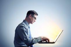 Προγραμματιστής ατόμων στο πουκάμισο και γυαλιά που κάθονται σε ένα lap-top Στοκ Φωτογραφίες