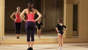 Προγύμναση ενός μικρού κοριτσιού στη γυμναστική Το κορίτσι μαθαίνει να υποκύπτει Ο δάσκαλος διδάσκει τη χορογραφία απόθεμα βίντεο