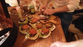 Προετοιμάζοντας τα χάμπουργκερ, που κατασκευάζουν το χάμπουργκερ, συστατικά για τα burgers μαγειρέματος στον ξύλινο τεμαχίζοντας  στοκ φωτογραφία