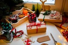 Προετοιμαμένος για τις διακοπές, τυλιγμένα δώρα στο έγγραφο της Kraft, ετικέτες για την υπογραφή, που περιβάλλεται από τα μικροπρ στοκ εικόνες