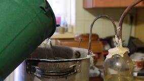 Προετοιμασία ένα λαθραίο ποτό στο σπίτι, διαδικασία απόσταξης Αντικατάσταση του ζεστού νερού στο κρύο στο σύστημα ψύξης, λαθραίο  απόθεμα βίντεο