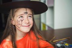 Προετοιμασία για αποκριές παιδί σε μια εξάρτηση μαγισσών που κάνει τη ζωγραφική προσώπου χαριτωμένη αράχνη ιδέα του απλού κοστουμ στοκ φωτογραφίες με δικαίωμα ελεύθερης χρήσης