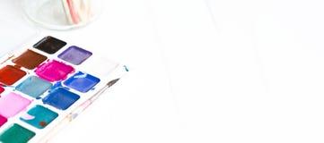 Προετοιμασία για τη δημιουργικότητα desktop Στον πίνακα είναι χρώματα, βούρτσες σε ένα άσπρο υπόβαθρο πανόραμα στοκ εικόνα με δικαίωμα ελεύθερης χρήσης