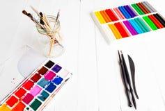Προετοιμασία για τη δημιουργικότητα desktop Στον πίνακα υπάρχουν χρώματα, βούρτσες, plasticine, σωροί στοκ εικόνα