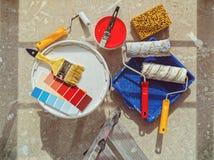Προετοιμασία για τη ζωγραφική των εργασιών Οι τράπεζες με το χρώμα, τις βούρτσες και τους κυλίνδρους είναι στο τσιμεντένιο πάτωμα Στοκ εικόνα με δικαίωμα ελεύθερης χρήσης