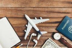 Προετοιμασία για τη διακινούμενη έννοια, μολύβι, ρολόι, χρήματα, διαβατήριο, αεροπλάνο, σημειωμένο βιβλίο, ακουστικό Στοκ Εικόνες
