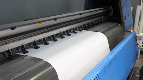 Προετοιμασία για τον Τύπο εκτύπωσης Inkjet μεγάλος-σχήματος Τα αρσενικά χέρια του εργαζομένου παρεμβάλλουν το καθαρό έγγραφο εκτύ φιλμ μικρού μήκους