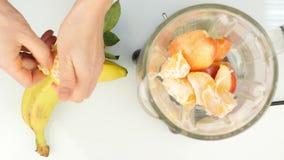 Προετοιμασία ενός κοκτέιλ φρούτων σε ένα μπλέντερ, καταφερτζήδες Τοπ όψη Ικανότητα και υγιής έννοια τρόπου ζωής 4K απόθεμα βίντεο
